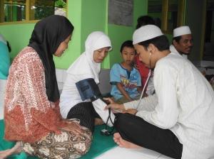 Mas Abdullah -alumni D4 Anestesi Jurs. Keperawatan- sedang memeriksa tensi seorang pasien yankes